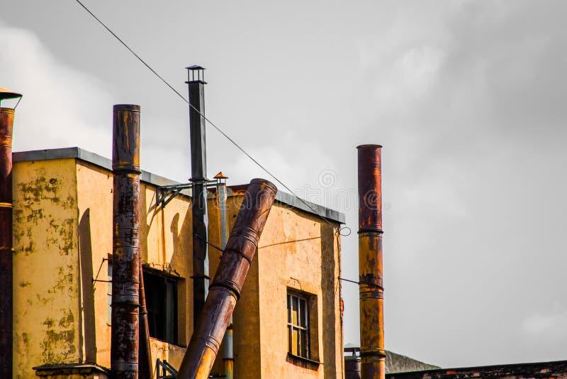 Costruzione con i vecchi tubi della ruggine del metallo ed il cielo grigio fotografie stock