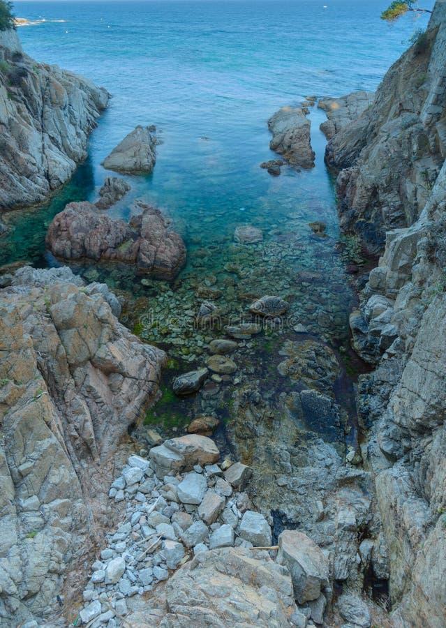 Costruzione con la costa rocciosa dell'arco & il mare traslucido fotografia stock libera da diritti