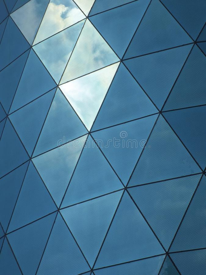 Costruzione corporativa moderna con i vetri di finestre rispecchiati modellati angolari che riflettono il cielo e le nuvole immagini stock libere da diritti