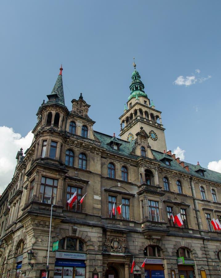 Costruzione del municipio con le bandiere rosse e bianche nazionali in Klodzko, immagini stock libere da diritti