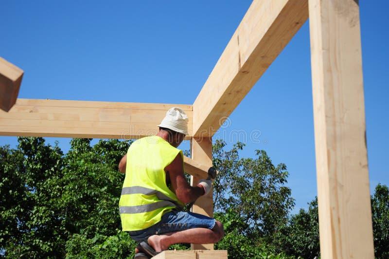 Costruzione del tetto della casa della costruzione del Roofer con il fascio di legno immagini stock