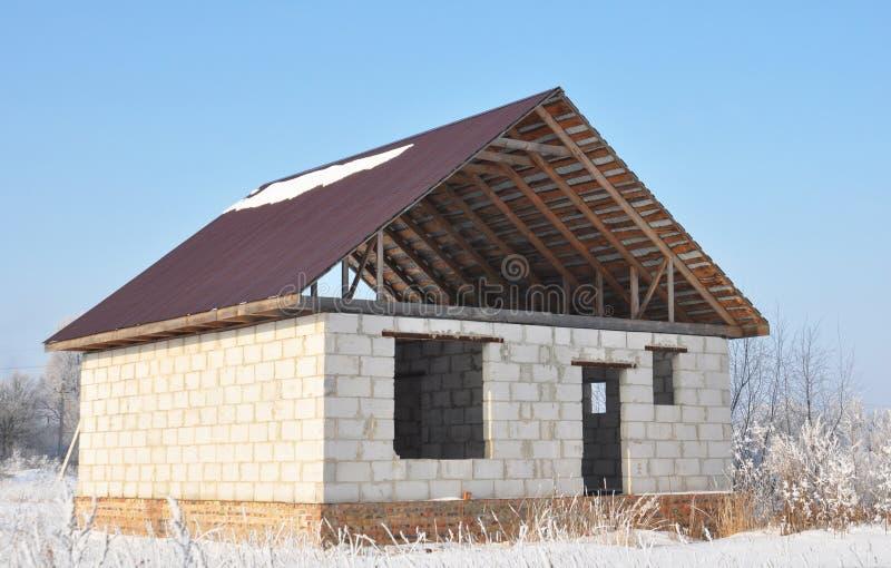 Costruzione della casa con il tetto del metallo, capriate, travi nell'inverno fotografia stock libera da diritti
