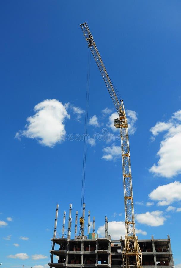 Costruzione della gru Gru a torre nel cantiere Gru gialla che sviluppa alto aumento immagini stock libere da diritti