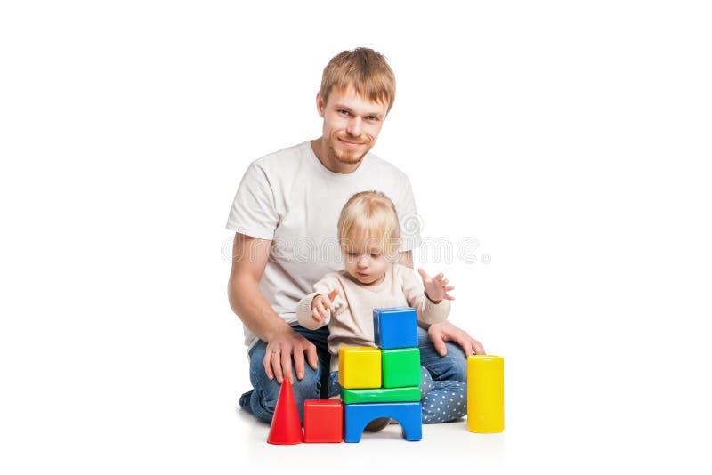 Costruzione della neonata dai blocchetti del giocattolo con suo padre fotografia stock