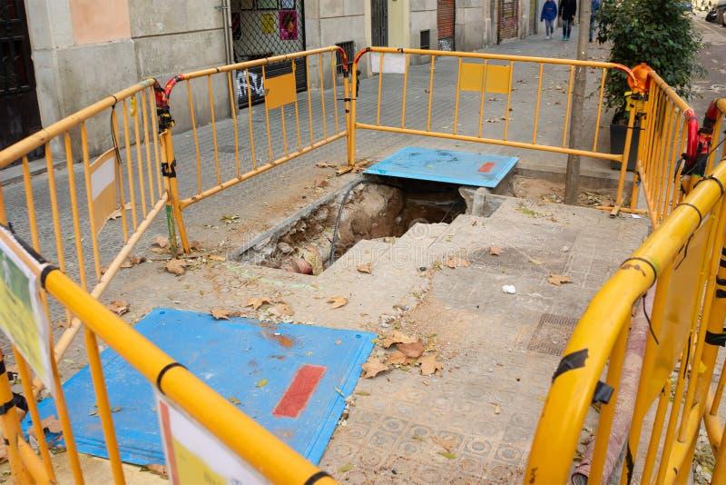 Costruzione della via lavoro il foro nel recinto giallo a terra fotografia stock libera da diritti