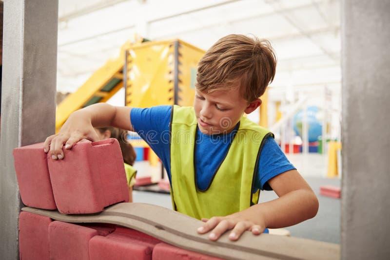 Costruzione dello scolaro con i mattoni del giocattolo ad un centro di scienza fotografia stock