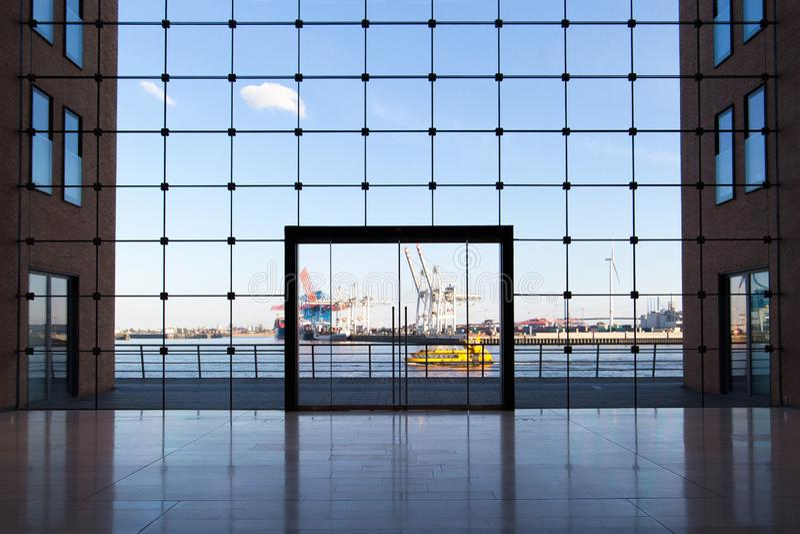 Costruzione di affari a Amburgo con le grandi finestre e una vista del porto famoso immagini stock