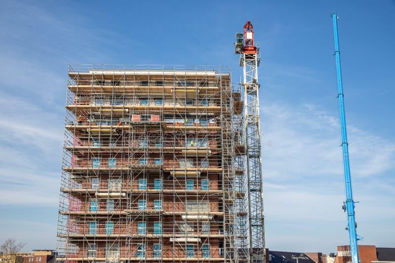Costruzione di appartamento del cantiere nuova con i lavoratori del muratore e dell'armatura fotografia stock libera da diritti