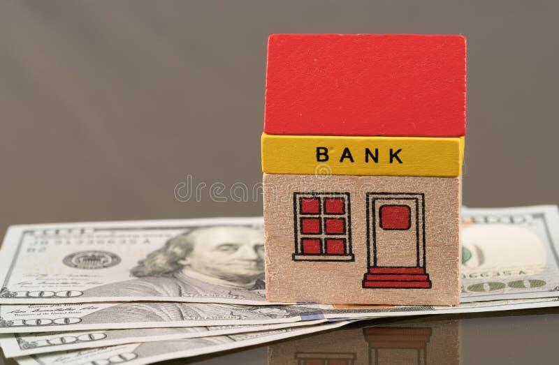 Costruzione di banca del giocattolo sui beni del dollaro americano immagini stock libere da diritti