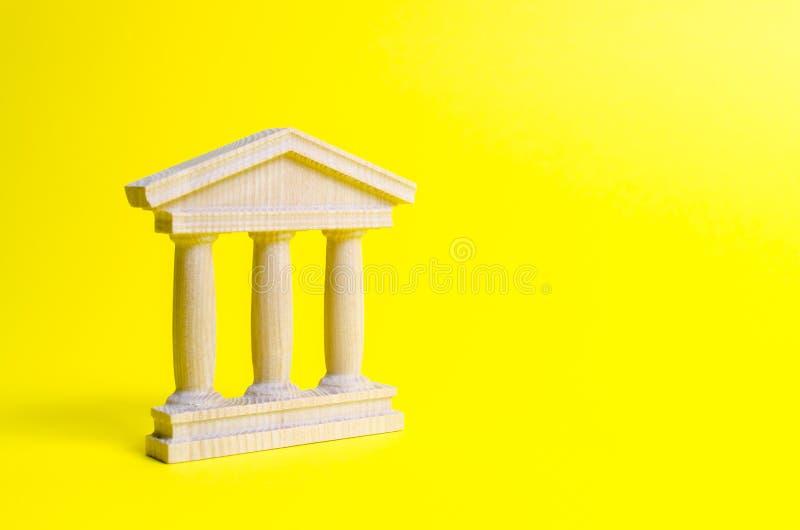 costruzione di legno di governo su un fondo giallo Le autorità, la sovranità del paese e lo Stato di diritto fotografie stock