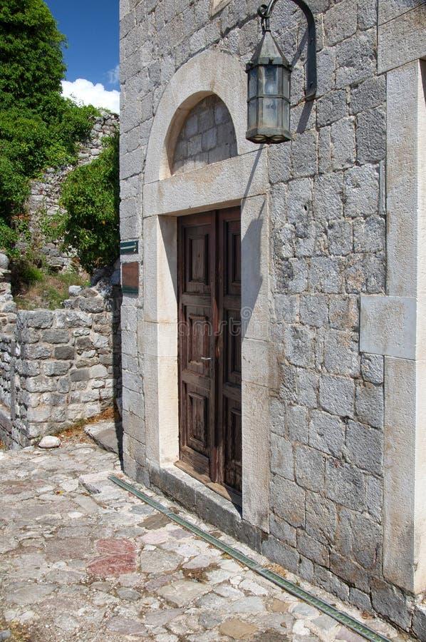 Costruzione di mattone antica nella vecchia barra della fortezza, Montenegro Porta di legno antica e vecchia lanterna immagine stock libera da diritti