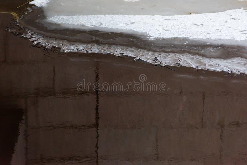 Costruzione di mattone riflessa nell'acqua fotografie stock