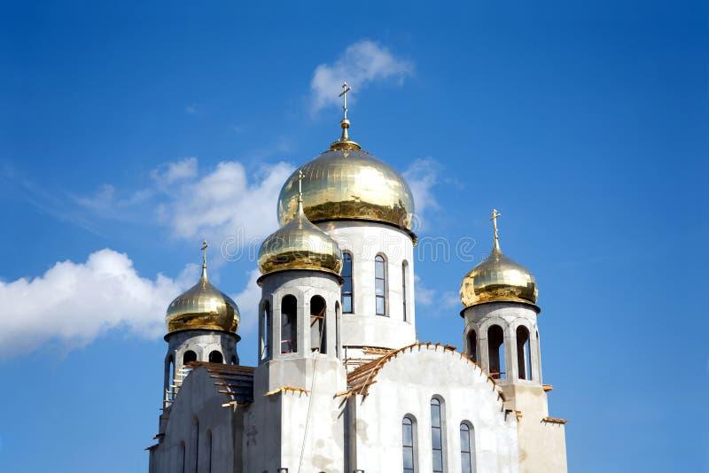 Costruzione di nuovo tempio con le cupole dell'oro contro cielo blu fotografia stock