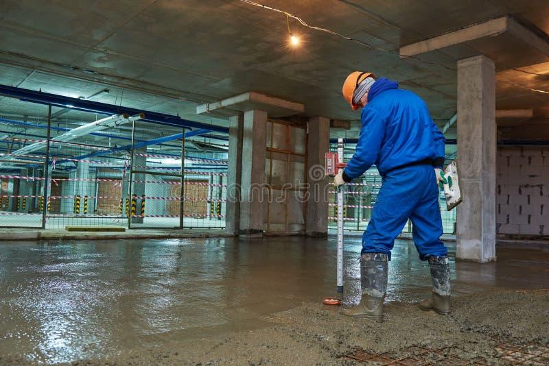 Costruzione di pavimento di calcestruzzo Lavoratore con la linea fotografia stock libera da diritti