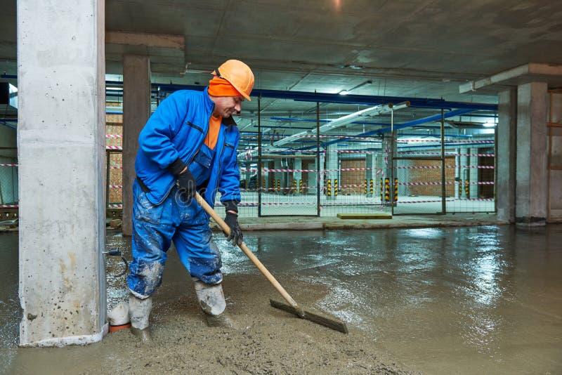 Costruzione di pavimento di calcestruzzo Lavoratore con screeder fotografia stock