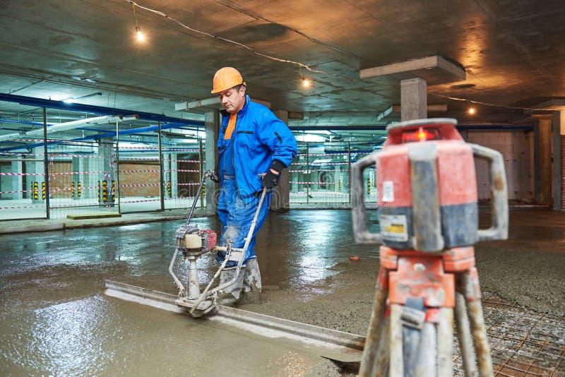 Costruzione di pavimento di calcestruzzo Lavoratore con screeder fotografia stock libera da diritti