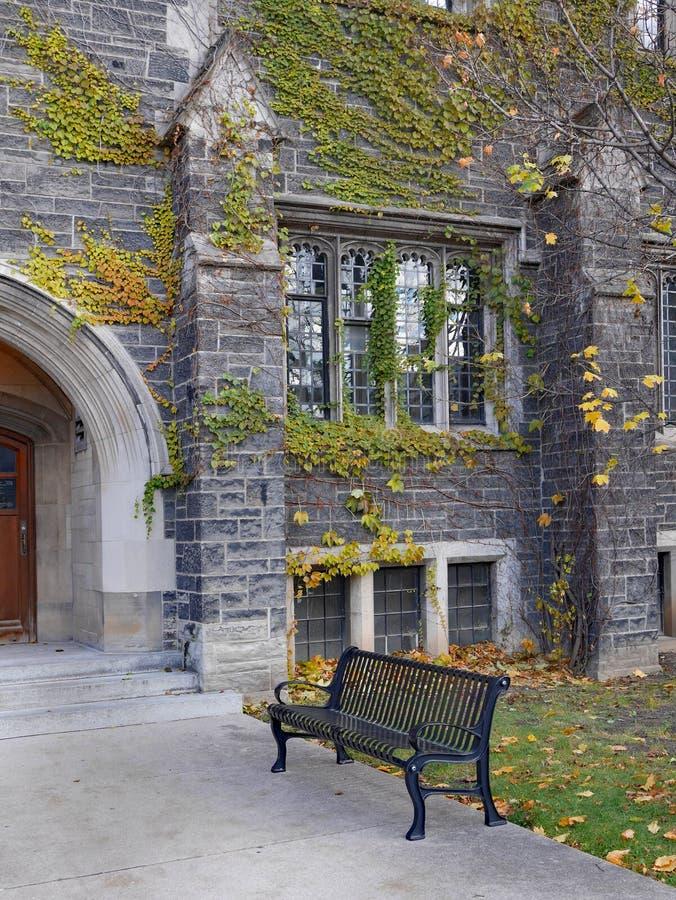 Costruzione di pietra dell'istituto universitario di stile gotico con il banco fotografia stock
