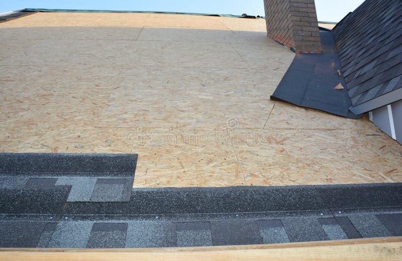 Costruzione di tetti con installazione di tegami di asfalto in un'area ad angolo soffitto con tetto di casa Sfide di asfalto in f fotografia stock libera da diritti