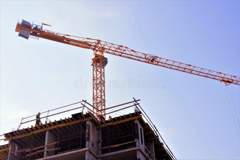 Costruzione di un edificio residenziale comodo di palazzo multipiano con una gru affidabile Costruzione di costruzione-architetto immagini stock libere da diritti