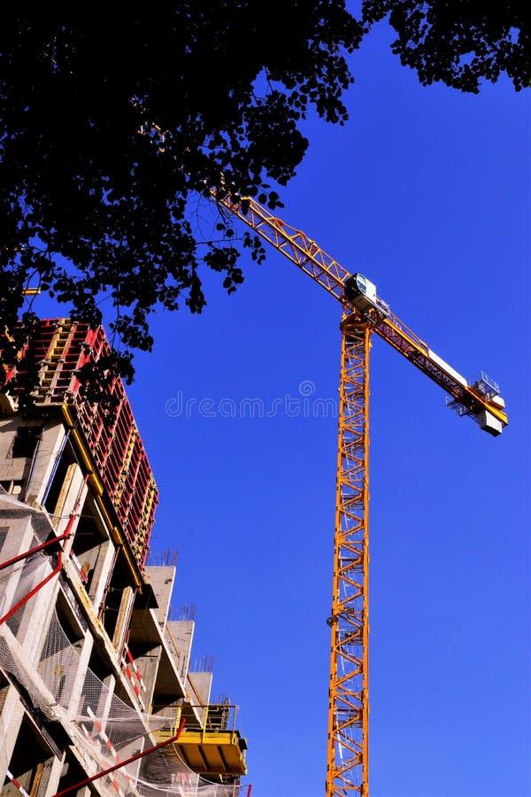 Costruzione di un edificio residenziale comodo di palazzo multipiano con una gru a torre Costruzione di struttura-architettonico, fotografia stock