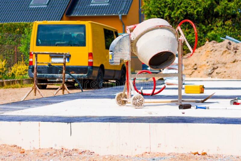 Costruzione di una casa e di una betoniera sui fondamenti della casa fotografia stock libera da diritti