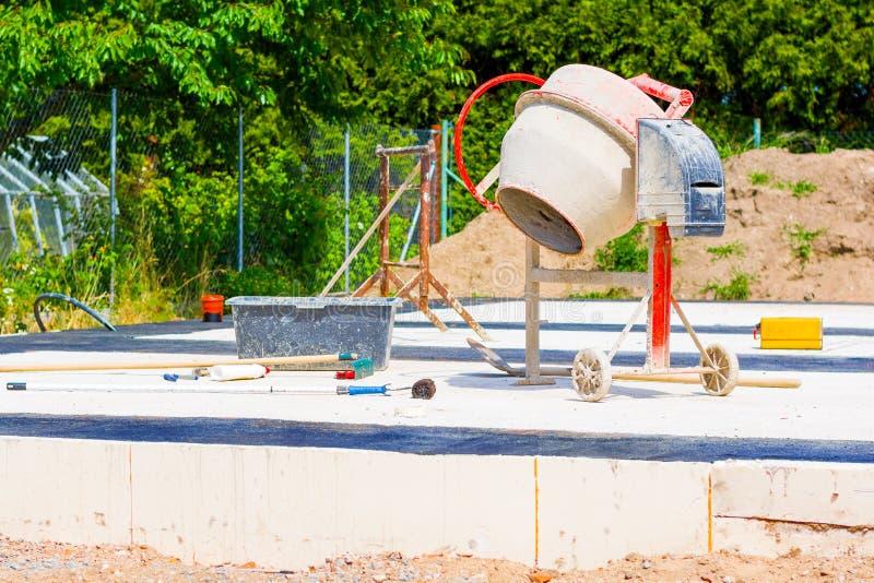Costruzione di una casa e di una betoniera sui fondamenti della casa immagini stock libere da diritti