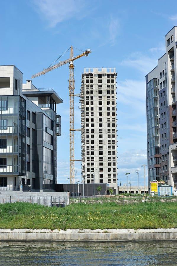 Costruzione di una casa mattone-monolitica moderna e di una gru di costruzione immagini stock
