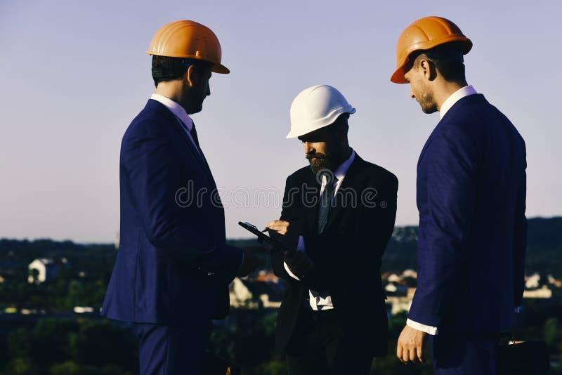 Costruzione e concetto di ingegneria Gli uomini con la barba ed i fronti concentrati fanno le note Cartella e penna della clip de fotografie stock