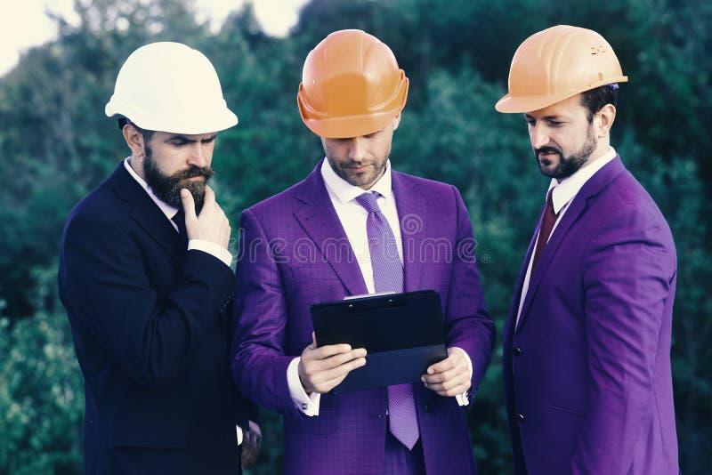 Costruzione e concetto di ingegneria I capi con la barba ed i fronti interessati discutono il progetto fotografia stock libera da diritti