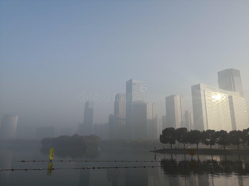 Costruzione e lago nell'ambito di luce dell'alba immagini stock