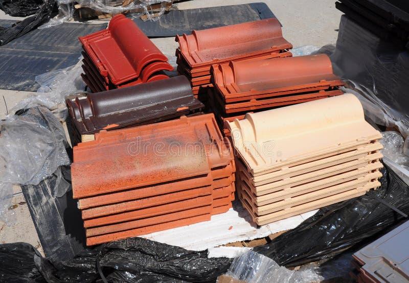 Costruzione e materiali da costruzione, mattonelle di tetto colorate organizzate sui pallet da vendere immagine stock libera da diritti