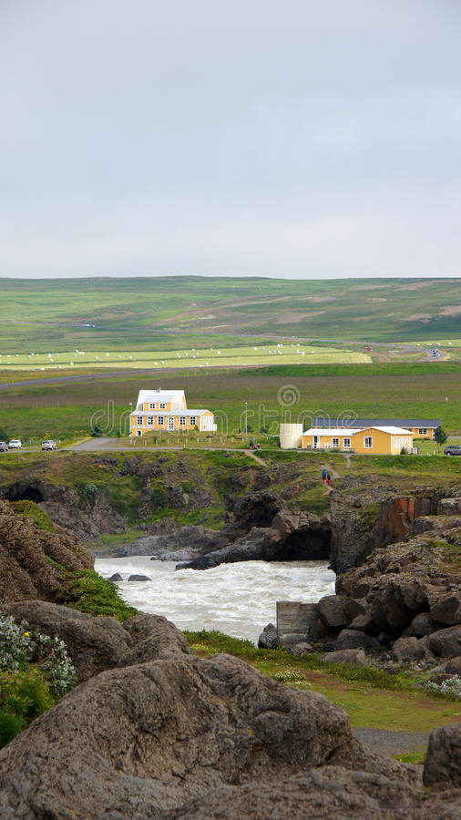 Costruzione gialla alla cascata di Godafoss in Islanda fotografia stock