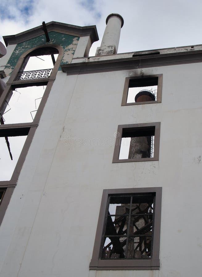 Costruzione industriale rovinata alta della fabbrica con i camini ed il metallo torto visibili attraverso le finestre vuote immagini stock