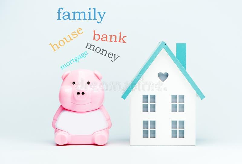 Costruzione, ipoteca, investimento, bene immobile e proprietà - casa di modello e un porcellino salvadanaio fotografie stock