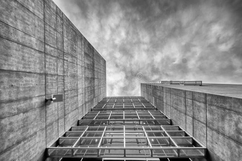 Costruzione moderna astratta e un cielo nuvoloso grigio fotografia stock libera da diritti