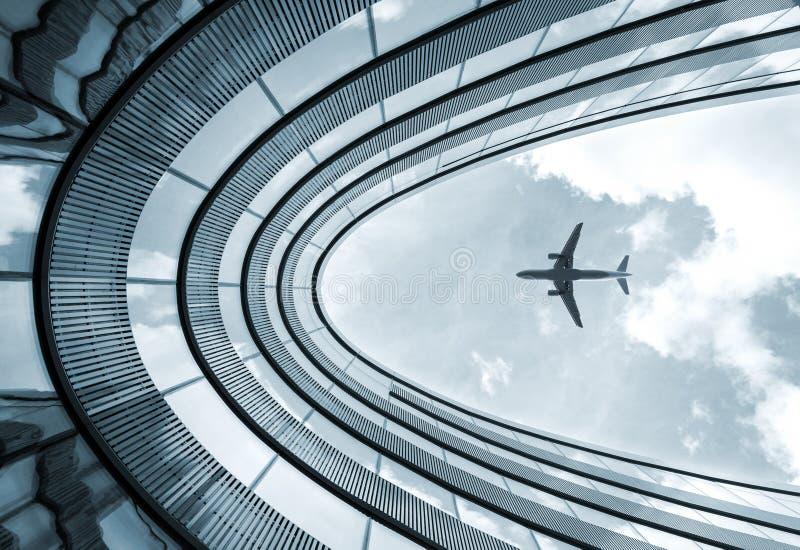 Costruzione moderna di architettura con l'aeroplano di atterraggio immagini stock libere da diritti