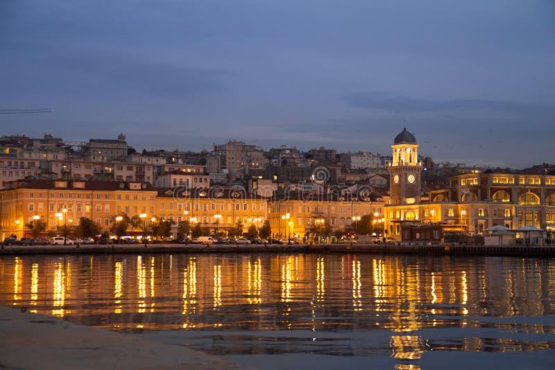 Costruzione nella sera sulla costa adriatica con la riflessione sull'acqua, Trieste, Italia immagini stock