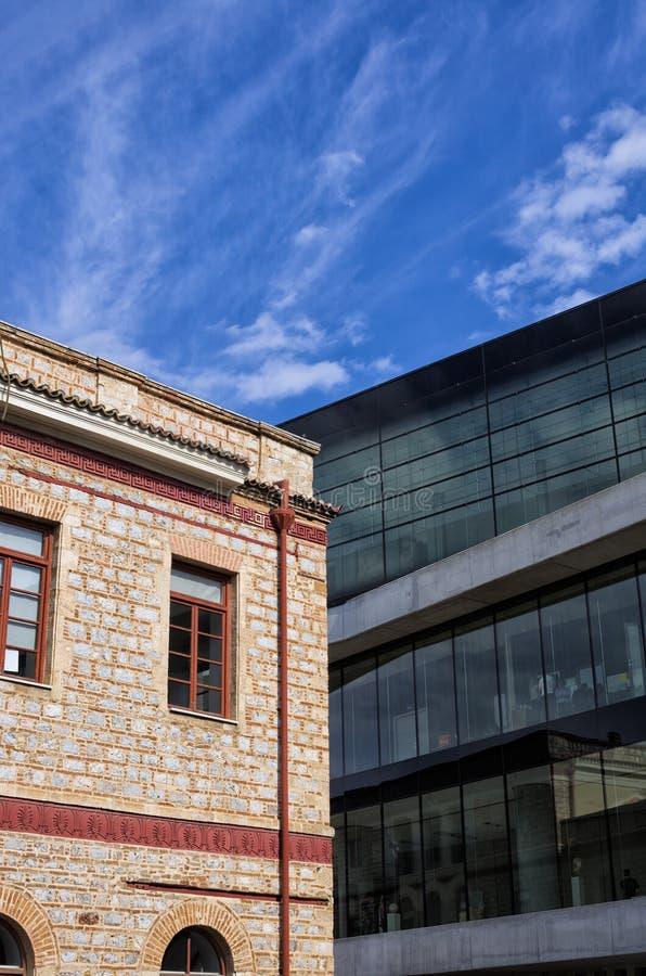 Costruzione neoclassica invecchiata contro l'architettura moderna, a Atene, la Grecia fotografia stock