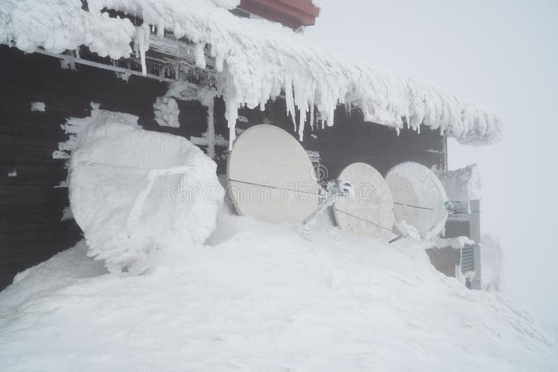 Costruzione nera in montagne coperte di neve e di ghiaccio, durante il giorno molto freddo nell'inverno immagine stock