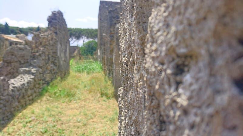 Costruzioni antiche a Pompei che scompare al punto di sparizione sotto il cielo blu immagini stock