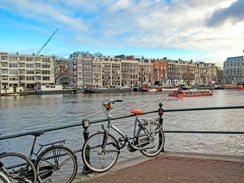 Costruzioni di mattone fiamminghe tradizionali olandesi famose di Amsterdam e della bici sul canale fotografia stock