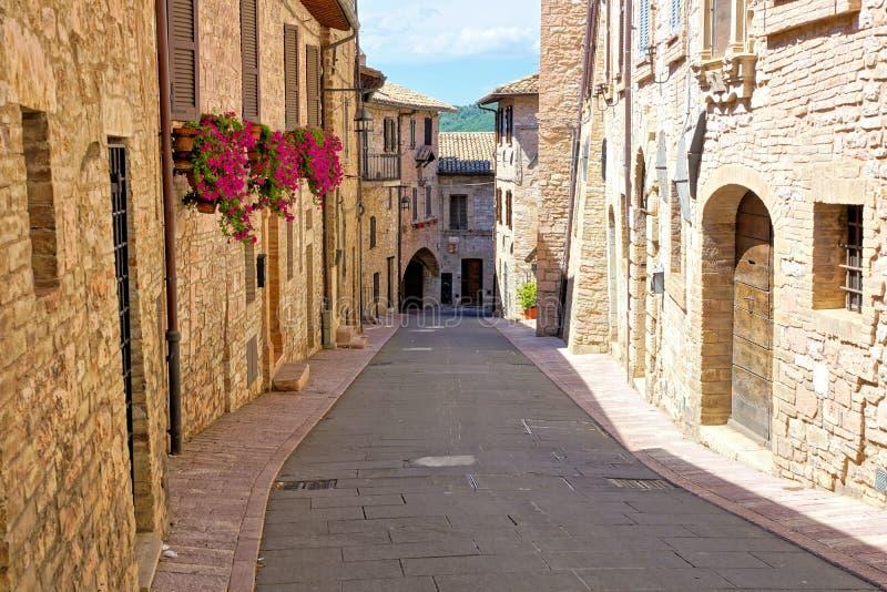 Costruzioni di pietra che allineano una via medievale nella vecchia città di Assisi, Italia fotografia stock libera da diritti