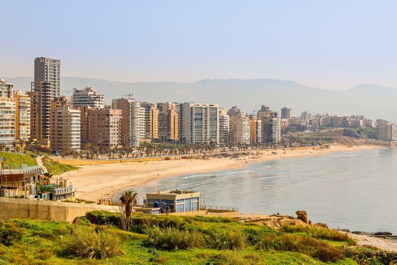 Costruzioni e torri del centro con la strada, la spiaggia sabbiosa ed il mare nella priorità alta, Beirut, Libano fotografia stock