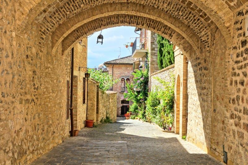 Costruzioni medievali di vecchia città di Assisi attraverso un arco di pietra, Italia fotografia stock