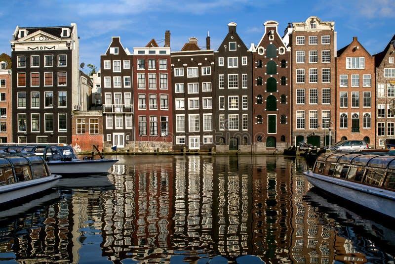 Costruzioni medievali olandesi tradizionali dentro lungo il lato del canale, riflesso in acqua Giorno pieno di sole Amsterdam, Pa fotografia stock