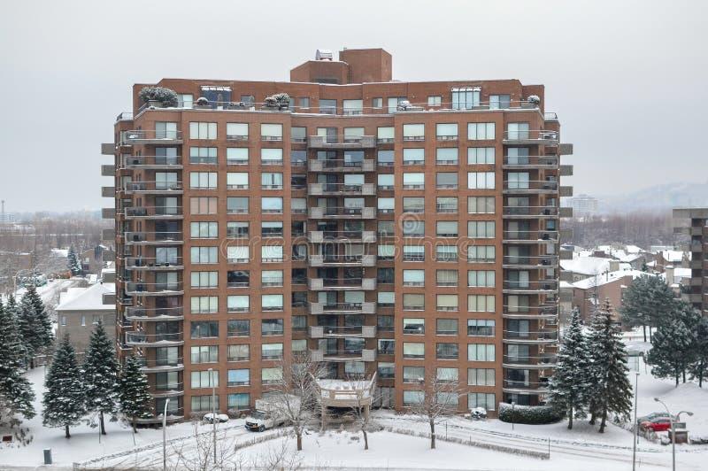 Costruzioni moderne del condominio con le finestre enormi in neve immagine stock
