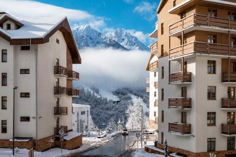 Costruzioni multipiano con le viste dei picchi di alta montagna un chiaro giorno soleggiato nell'inverno immagini stock