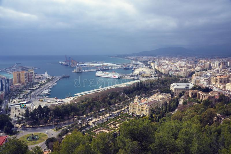 Costruzioni, porto, baia, navi e montagne contro un cielo nuvoloso Cielo drammatico sopra la città Bella vista immagine stock