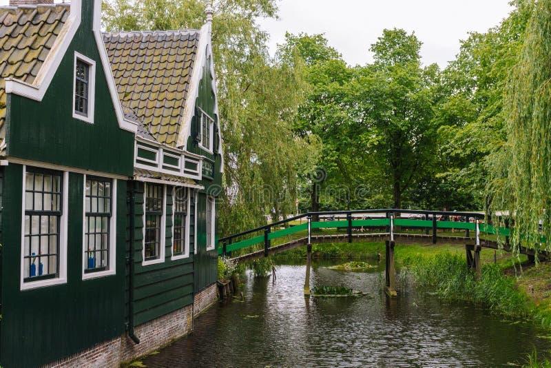 Costruzioni rurali di legno con il ponte di legno e gli alberi Paesaggio idilliaco della campagna Belle case vicino al canale fotografie stock