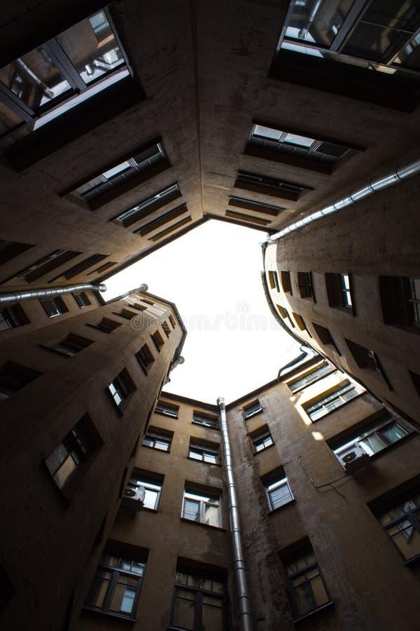Costruzioni strette bene a St Petersburg con il cielo sopra i tetti Sotto la vista immagine stock libera da diritti